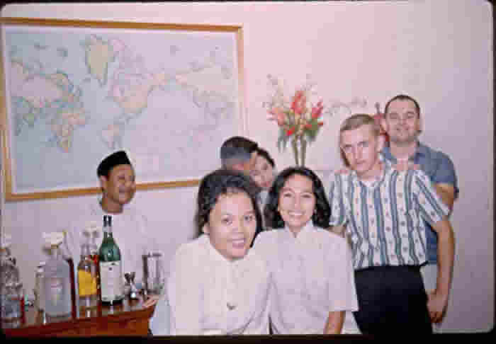 Local Scene - in my home, bartender Sieman (house boy) and Embassy personnel and members of Pangemanan family.